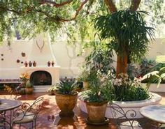 Lush Spanish style patio with saltillo tile floor and stucco fireplace ...