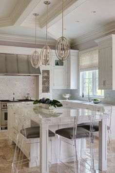 Gorgeous kitchen with marble island, translucent bar chairs and pretty pendant lighting | Buckingham Interiors + Design LLC
