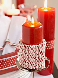 wrap with double stick carpet tape and press candy canes onto the tape around candle