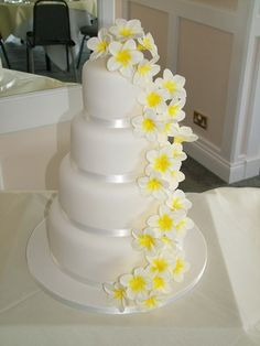 custom white fondant classic elegant traditional wedding cake design with white and yellow sugar flowers.