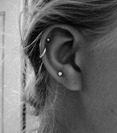 The asymmetry of an odd number of earrings plays up the look's natural edginess. Two cartilage piercings on one ear, one plus tragus on the other. Three piercings on the lobe. Definitely what I want Helix Piercings, Piercing Oreille Cartilage, Ear Peircings, Cute Ear Piercings, Piercing Tattoo, Double Helix Piercing, Helix Hoop, Helix Ring, Unique Piercings