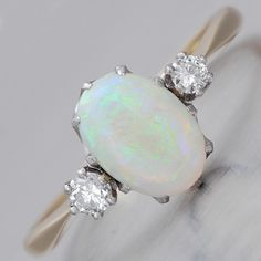 In enchanting, immaculately designed period style, this vintage 18k gold and platinum 1950's English ring of unmistakable delicacy and aesthetic beauty exposes a 0.89ct ovular opal cabochon flanked by a glowing duo of prong-set modern brilliant-cut diamonds, cumulatively weighing 0.14cts, graded H-I color and SI1 clarity. The latter are mounted in platinum.