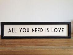 """Cuadro """"All you need is love"""". Marco de madera color negro y lámina interior de color crema con el texto """"ALL YOU NEED IS LOVE"""". El marco tiene pequeños toques de efecto desgastado en los bordes para dar un aspecto vintage. Dimensiones 46x11cm East of India"""