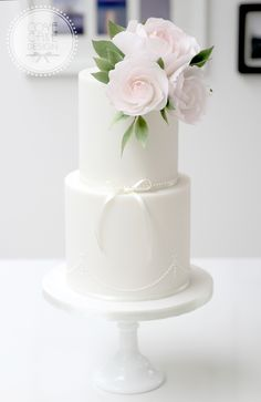 White wedding cake with piping detail and oversized sugar roses