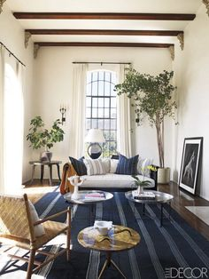 For the living room of actress Ellen Pompeo's Hollywood villa, Martyn Lawrence Bullard dressed a custom-made sofa with pillows covered in Indian cotton throws. The Afghan wool dhurrie is from the 1930s, and the candelabra is by Picasso. - ELLEDecor.com