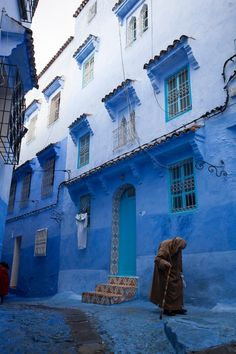An elderly gentleman walks the blue streets of the medina in Chefchaouen, Morocco.