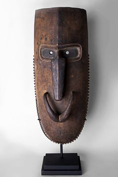 Stylized Manam Island Mask This large hardwood Manam Island mask possesses classic deep set eyes and a long angular curved nose. The piece displays serrated edging along the outer lower section. Dark circular decoration remains above the eyes. There is a glossy patina upon the nose from handling over time.