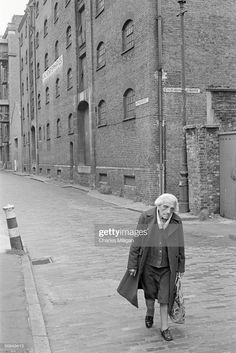 A elderly woman walking down Wapping High Street in the Docklands area of east London, circa Behind her are the warehouses of King Henry's Wharves. Get premium, high resolution news photos at Getty Images East End London, Old London, Iconic Photos, Old Photos, The Artist's Way, Irish Catholic, Tower Hamlets, Liverpool History, Industrial Architecture