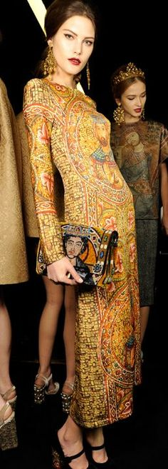 Dolce & Gabbana F/W 2013 backstage. She is dressing what could easily resemble a dalmatic, a heavily decorated long sleeve tunic.
