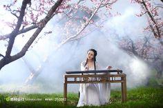 桃花树林中弹古筝的古典美女--干露露
