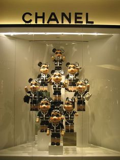 Its a theme pile up display showcasing the signature USP of Chanel, black tweed coat and skirt with gold liniing The BANNER is golden and black which is synonymous withe the brand The DIRECTION is from bottom to top as it is on stacks The LIGHTING is general