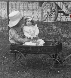 Vintage Photo of a Little Girl Gazing At Her Doll While Sitting in Her Wagon