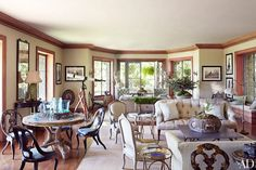 An expansive space is broken up into multiple seating areas.  Table w/ chairs on left.  Martha Stewart Maine Estate