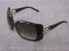 bcc919a55ea Gucci tortoise sunglasses. Multi brown resin frames with light brown lens.  Feature gold GG