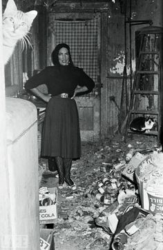 "1972  ""Little Edie"" from Grey Gardens poses in her house filled with garbage.  Nice cat photo bomb"