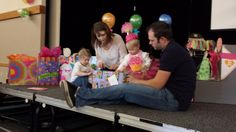 Birthday girl and fun party hat opening presents at the Candy Land First Birthday Party