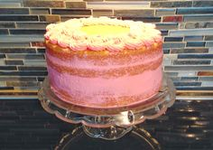 A nearly-naked hot milk cake with European buttercream and pink rosettes