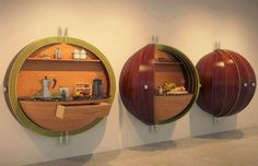 Part secret room, part cool kitchen workspace, all curved and completely semi-spherical this is one strange but creative way to solve your kitchen storage issues – a hanging half-circle cabinetry unit that holds (and hides) extra space right on your wall.