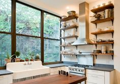 rustic shelving, sink, countertops, and tall windows