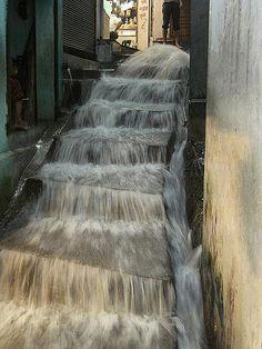 Uma forte chuva transformou uma escada em cachoeira na cidade de Rishikesh, estado de Uttaranchal, Índia. Excelente para limpar os sapatos.  Fotografia: