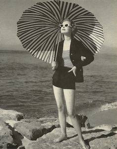 this photo is obviously taken in the 1950's because of the style of clothing and the pattern on the umbrella.
