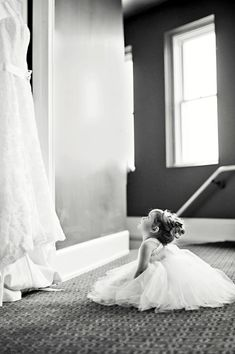 i know I pin a lot of flower girl poses, but they're just so darn cute! Flower girl looking at wedding dress.