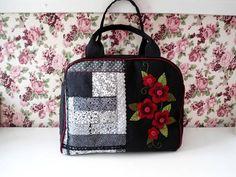 Bolsa exclusiva em preto com aplicação de flores vermelhas e patch em preto com aplicação.