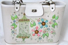 This is a wonderful Enid Collins Rain Drops canvas bucket purse. It is marked inside with the Copyright The Original Collins of Texas, Inc. Lovely pastel Springtime colors with the aurora borealis pink, green, and blue floral jewels, yellow or amber rhinestone centers, little white, pink and blue accent flowers and tiny rain drop rhinestones. It has a canvas body with a wood bottom. Zippered pocket inside.  Measures approx. 8 1/2 tall by 12 long and double handle drop is approx. 6.  Does...