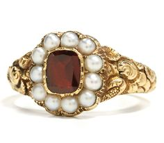 Pearl and garnet ring, probably English, c. 1830. Within the warmth of antique gold a rectangular cut garnet settles in repose amidst the embrace of a rub over pinched collet as a surround of natural half pearls exposes a lustrous inner light. Please take note of the delicate and fine crimping along the perimeter of the pearls – stylistically typical for this period. The well proportioned shank displays the deeply chased with flower motif that is often associated with English workmanship…