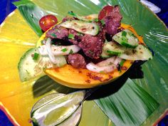 Beef Polynesian features seared and well-seasoned beef tenderloin in a grilled Hana papaya with a wedge of lime to squeeze over the whole dish. Island Mama's Fish House in Maui.