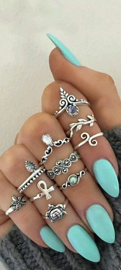 Silver stacked rings and teal nails