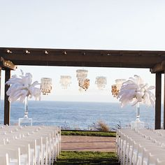 """Brides.com: . Capiz Shells and Feathers. For a sunset ceremony held atop a bluff, Julie Hsu wanted the décor to complement the Pacific Ocean backdrop. """"We thought flowers would simply pale in comparison to the panoramic views,"""" she says. """"Plus, we wanted to incorporate natural elements in white to suit the beach setting."""" Capiz shell chandeliers suspended from the venue's pergola and tall arrangements of white feathers on translucent pedestals fit the bill perfectly. Décor by White Lilac…"""