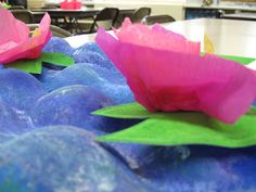 I love Claude Monet.  I love teaching students about him and his art work.  I came up with the idea to paint a Monet lily pond from an inspiring post from Painted Paper.              First my 4th grade students painted blue apple trays in Monet style using a variety of blue tempera paints, violet, green, white, pearl it and texture it paint mediums.              I told them to make sure to paint the whole tray, even the sides!                  Students then made lily pads with green painted…