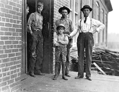 This boy has worked in Payne Cotton Mill, for 2 yrs Macon, Georgia. Runs 4 sides and earns 52 cents a day. Overseer has hand on boy's shoulder, 1909