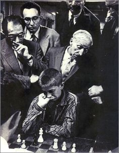 Bobby Fischer plays chess in New York, 1957; older men watch, making faces.