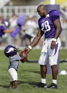 8b1483ab6 Minnesota Vikings running back Adrian Peterson hands a football to his son  Adrian Jr. at