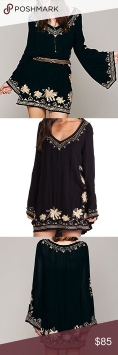 FREE PEOPLE SKYFALL EMBROIDERED  V-NECK DRESS The Free People Skyfall V-neck dress brings you a flowing silhouette and floral embroidery. Cinch at the waist with a belt for a more fitted look. Free People black dress with floral embroidered trim. V neckline. Long bell sleeves. Loose fit; pullover style. Rayon. Free People Dresses Mini