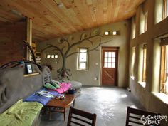 A Cob bench and South wall makes for a cozy living room. The Robinson's family home.