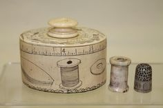 """Rare 1811 ivory oval scrimshawed sewing box with carved thimble and thread spool, fitted lid reads, """"Sarah Mills"""" in upper banner and """"My Sewing Box"""" in lower banner, """"1811"""" carved between lid knob, leaves and flowers also on lid, with a carved scrimshawed accurate tape measure around upper border of sides, sewing tools all around sides, cubed edging border on bottom of sides, 3 1/8"""" W x approximately 2 1/4"""" H. Thimble also has her name carved into side."""