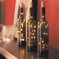 Strands of white lights in a wine bottle make for a classic display. Strip the labels off of three bottles and use battery powered LED lights to avoid having to cut into the glass Must do!