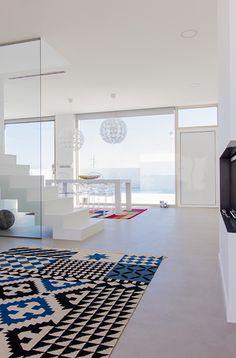 Chiralt Arquitectos I Salón con escalera de hormigón revestida con microcemento y barandilla de cristal.