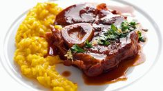 Ossobuco alla Milanese mit Safran-Risotto auf einem Teller serviert.