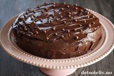 """Annonse: Adlibris Hei og god mandag! Jeg er på vei til London, men vil først gi dere en bra start på ny uke med oppskriften på en knallgod sjokoladekake! Kaken er rik på mørk sjokolade, som gir den ekte, gode sjokoladesmaken, og så er den fylt med en ekstra deilig sjokoladekrem som inneholder kremost (en amerikansk """"Chocolate Cream Cheese Frosting""""). Det nydelige, rosa kakefatet du ser på bildet, er fra den nye Kjøkken- og servise-kategorien til Adlibris. ENJOY!"""