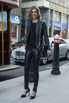 Arizona Muse in a black leather motorcycle jacket + black sweater + nude button-up + black leather leggings + black peep-toe heels