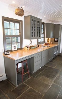Bold gray (similar to Benjamin Moore's Shaker Gray 1549) locks up a look from Kitchens by Design, pairing window trim and matching cabinets.