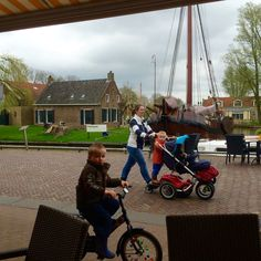 Old Dutch village with old Eel-fishingboat in background and youngster on bike passing.