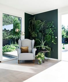 """""""While charcoal and navy will always have our heart, we see deep green hues coming to the fore,"""" says Waterman, who hails from Australia but now lives in New York. """"These shades offer a sense of peace and provide the perfect canvas to contrast earthy textures, leather, and wood."""" Play up the color with matching plants, as in this wall, """"for a verdant assault on your senses."""""""
