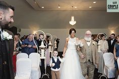 The bride is walked down the aisle by her dad & her son as her future husband looks on. Weddings at Tulfarris Hotel & Golf Resort. Photographed by Couple Photography.