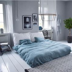 Gorgeous serence and calming bedroom from @nordenbergers with wooden floors painted white, light blue bedsheets and framed posters from printler.com, the marketplace for photo art.