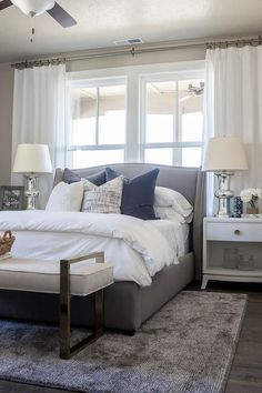 bedroom features a gray wingback bed with silver nailhead trim dressed in soft white ...